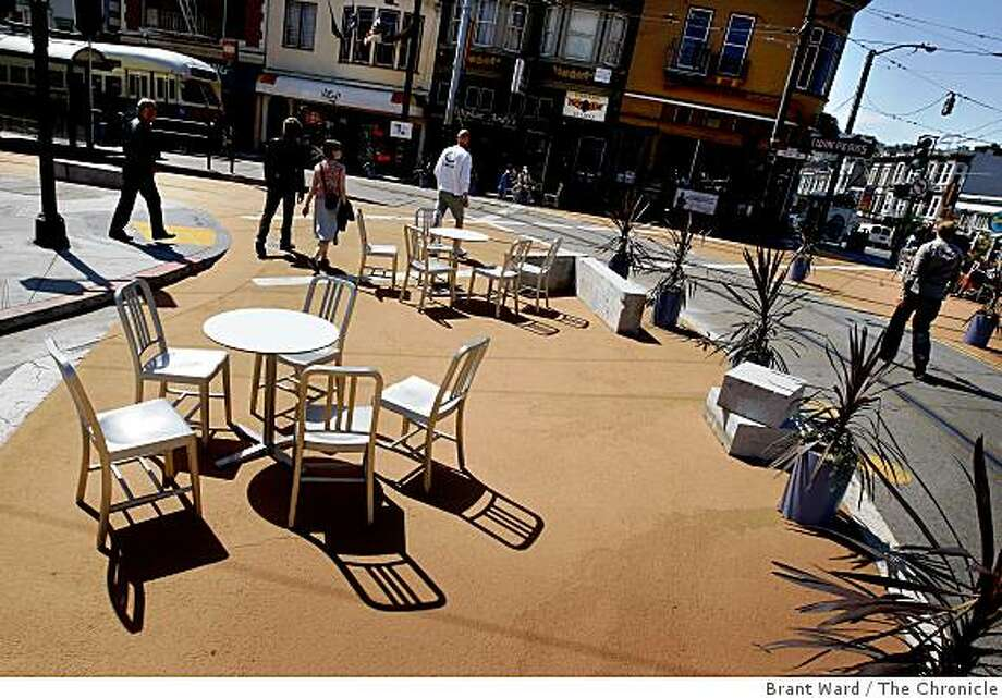 Tables and chairs cast shadows in the morning light as pedestrians make their way through the plaza. A temporary public plaza at the end of the streetcar line at 17th Street and Castro Streets in San Francisco, CA creates a place where people can linger and watch the world go by. Photo: Brant Ward, The Chronicle