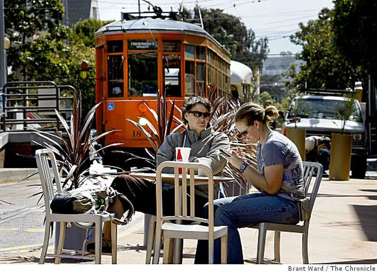 Stacy Fritz (left) and Candy Mitchell enjoy a snack at a table set up at the new plaza. They are visiting from the east coast. A temporary public plaza at the end of the streetcar line at 17th Street and Castro Streets in San Francisco, CA creates a place where people can linger and watch the world go by.