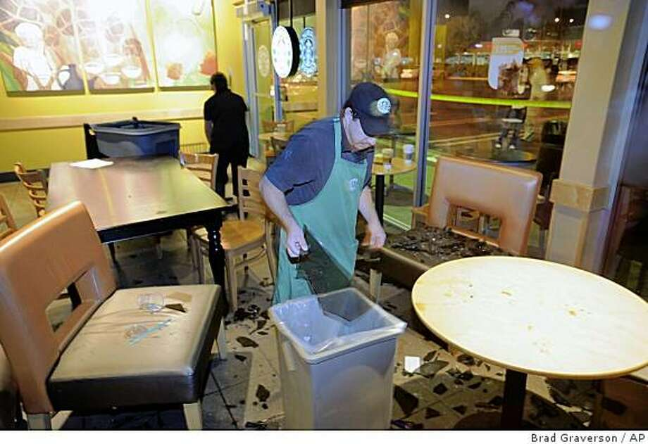 Workers inside a Starbucks coffee house in Torrance, Calif. clean up broken glass from the evening earthquake on Sunday, May 17, 2009. Photo: Brad Graverson, AP