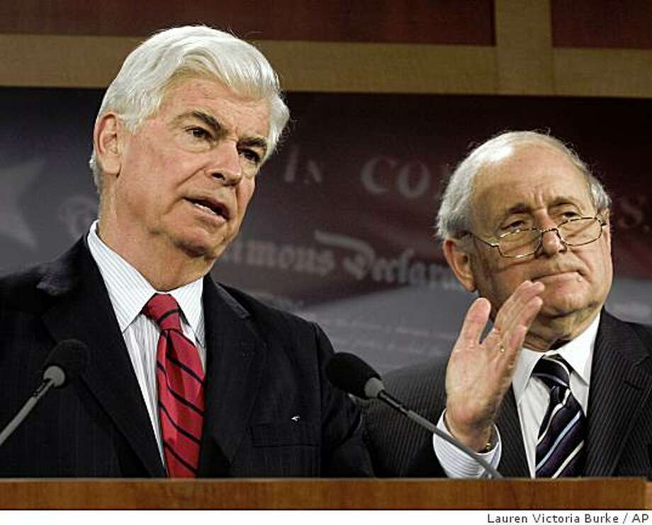 Senate Banking Committee Chairman Sen. Christopher Dodd, D-Conn., left, accompanied by Sen. Carl Levin, D-Mich., gestures during a news conference on Capitol Hill in Washington, Tuesday, May 19, 2009, after the Senate voted to prohibit credit card companies from arbitrarily raising a person's interest rate and charging many of the exorbitant fees that have become customary _ and crippling _ to cash-strapped consumers. (AP Photo/Lauren Victoria Burke) Photo: Lauren Victoria Burke, AP