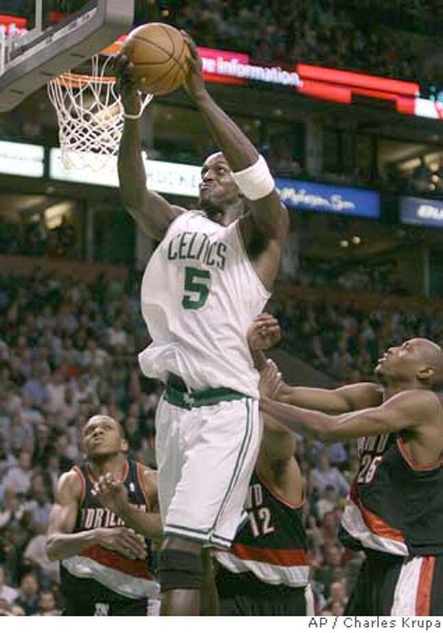 Boston Celtics forward Kevin Garnett (5) hauls down a rebound against Portland Trail Blazers forwards Travis Outlaw, right, Marcus Aldridge, center, and James Jones, left, during the first half of their NBA basketball game in Boston, Wednesday Jan. 16, 2008.(AP Photo/Charles Krupa) EFE OUT Photo: Charles Krupa