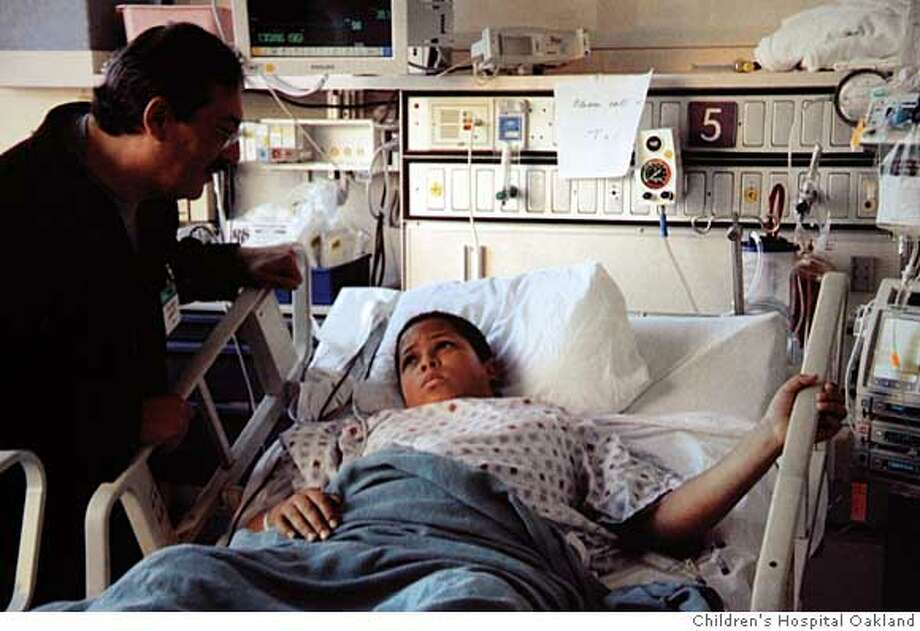 Photo of From left: Richard Rodriguez and Christopher Rodriguez taken yesterday, January 15, 2008 at Oakland Children's Hospital of Oakland. Photo Courtesy Children's Hospital & Research Center Oakland Ran on: 01-17-2008  Richard Rodriguez talks to his son, Christopher, who was hit by a stray bullet while at a piano lesson on Piedmont Avenue. Photo: Children's Hospital