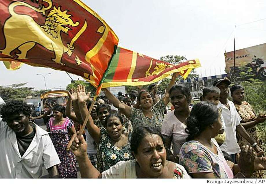 Sri Lankans hold national flags as they celebrate the victory of military over Tamil Tiger rebels in Colombo, Sri Lanka, Monday, May 18, 2009. Sri Lanka declared Monday it had crushed the final resistance of the Tamil Tigers, killing rebel chief Velupillai Prabhakaran and ending his three-decade quest for an independent homeland for minority Tamils. Photo: Eranga Jayawardena, AP