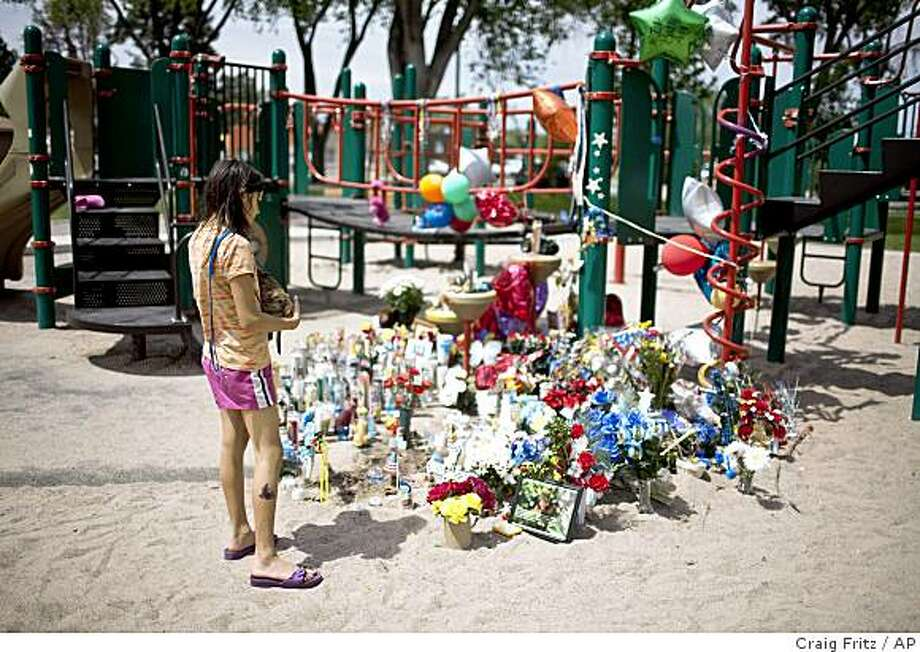 "Alexis Norris, looks over a memorial where the body of Tyruss ""Ty"" Toribio was found in Alvorado Park  in Albuquerque, N.M. on Thursday, May 21, 2009. Albuquerque Police announced the arrest of his mother Tiffany Toribio Thursday  for the murder of her son  Police said  that the mother of the 3-year-old boy who was found buried at the playground told investigators she suffocated him, had second thoughts and brought him back to life, then changed her mind and suffocated him again..(AP Photo/Craig Fritz) Photo: Craig Fritz, AP"