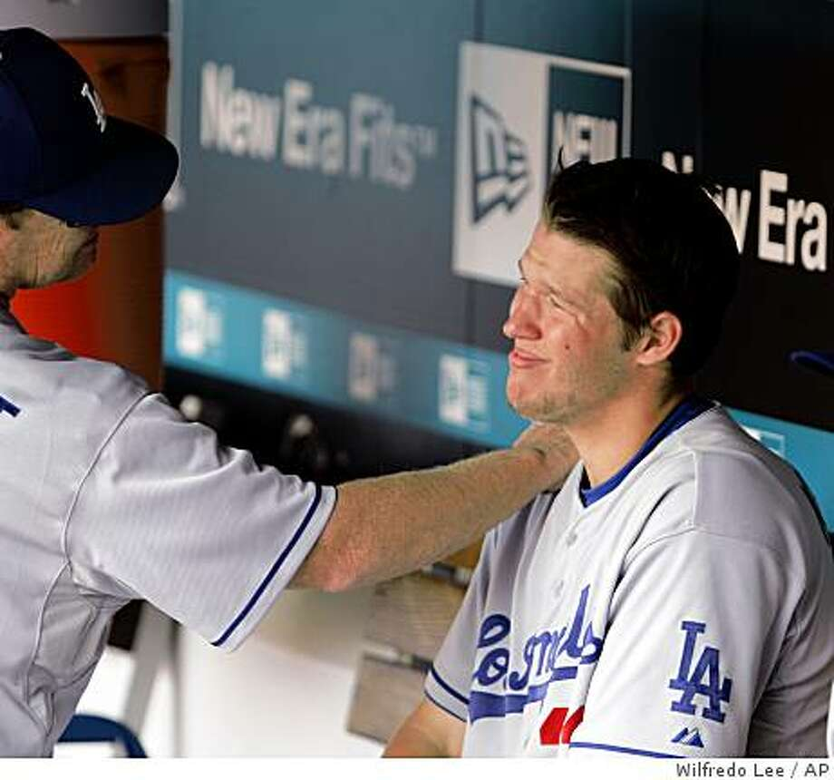 Los Angeles Dodgers pitching coach Rick Honeycutt, left, puts his hand on the shoulder of pitcher Clayton Kershaw, right after he left the game during the eighth inning of a baseball game against the Florida Marlins, Sunday, May 17, 2009, in Miami. Kershaw had a four-hitter as the Dodgers defeated the Marlins 12-5.  (AP Photo/Wilfredo Lee) Photo: Wilfredo Lee, AP