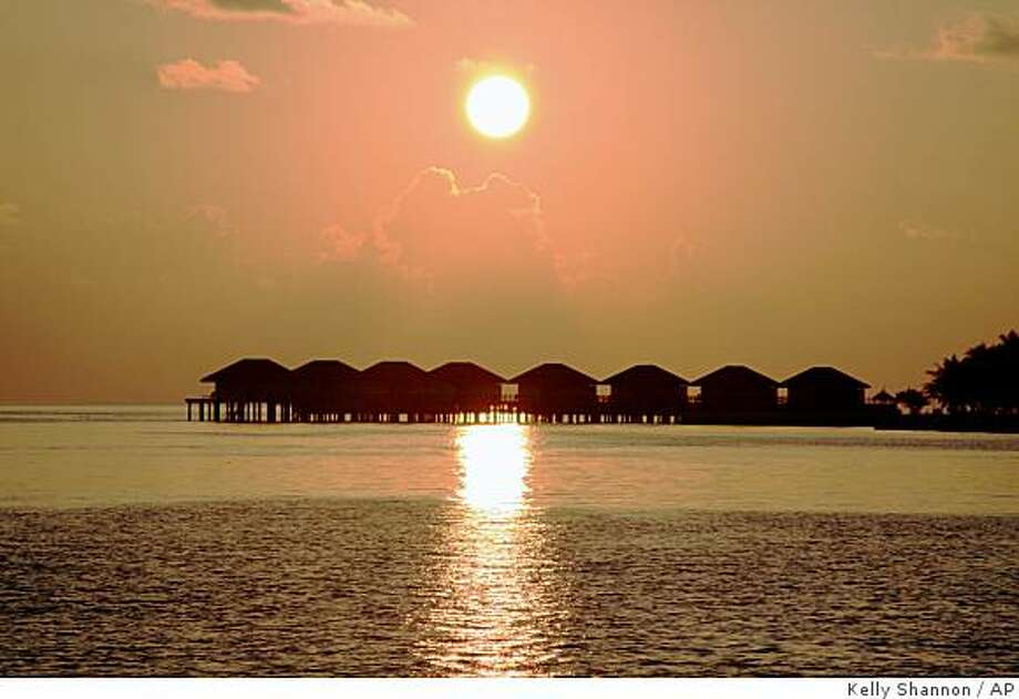 ** ADVANCE FOR SUNDAY, MAY 1 ** In this March 25, 2009 photo,  he sun sets over vacation cottages  in the Maldives.  Since climate change fears first gripped the globe, tourists have flocked to the Maldives to enjoy the islands' spectacular vistas before they vanish.  Scientists have long warned that the Maldives, an archipelago nation of nearly 1,200 islands in the Indian Ocean, will be wiped out by rising sea levels in the coming decades. (AP Photo/ Kelly Shannon) Photo: Kelly Shannon, AP