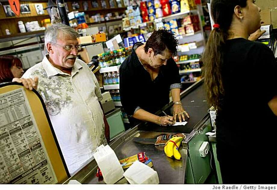 MIAMI - MAY 20: Marlene Woofter signs her credit card receipt as cashier Yera Dominguez charges the credit card for items at Lorenzo's Italian Market on May 20, 2009 in Miami, Florida. Larry Woofter stands to the left. Members of Congress today passed a bill placing new restrictions on companies that issues credit. The vote follows the Senate passage of the bill, which now heads for President Obama's promised signature. The bill will curb sudden interest rate increases and hidden fees, requiring card companies to tell customers of rate increases 45 days in advance. It will also make it harder for people aged below 21 to be issued credit cards.  (Photo by Joe Raedle/Getty Images) Photo: Joe Raedle, Getty Images