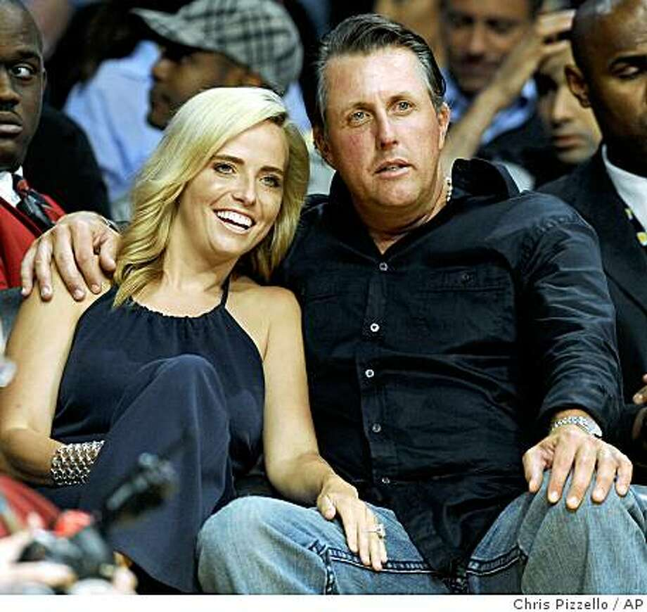 FILE - In this May 12, 2009 file photo, golfer Phil Mickelson and his wife, Amy, watch Game 5 of a second-round NBA playoff series between the Los Angeles Lakers and Houston Rockets in Los Angeles, Tuesday, May 12, 2009. Mickelson's wife, Amy, has been diagnosed with breast cancer, and the three-time major champion said Wednesday, May 20, 2009,  he will suspend his PGA Tour schedule indefinitely. (AP Photo/Chris Pizzello, File) Photo: Chris Pizzello, AP