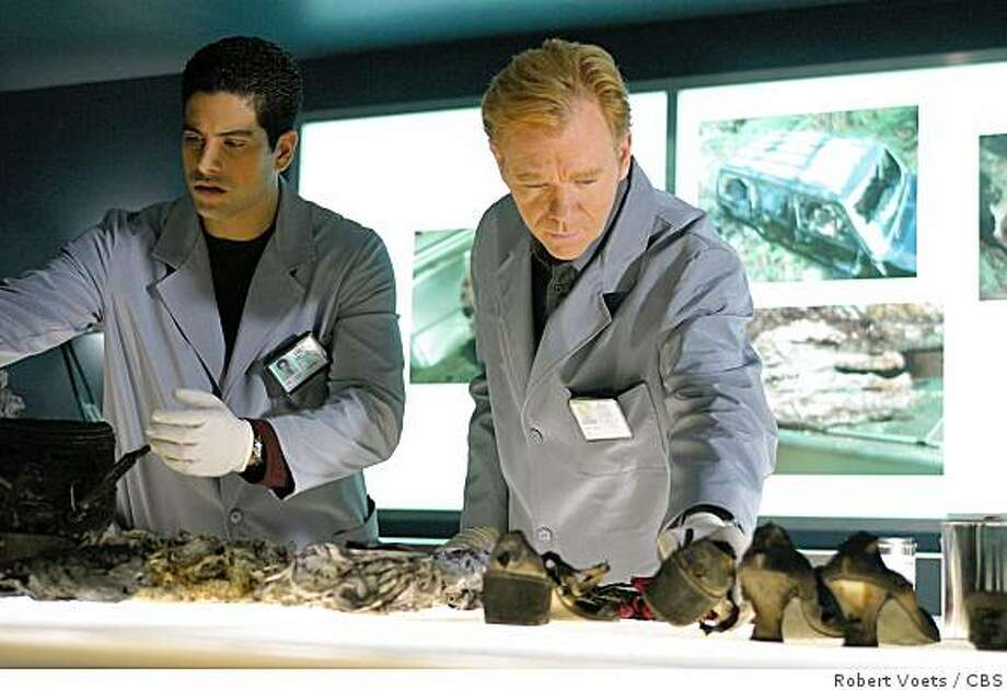 """THIS IS A HANDOUT IMAGE. PLEASE VERIFY RIGHTS. GOODMAN11a-C-09OCT02-DD-HO caption: """"Ashes to Ashes"""" -- Delko (Adam Rodriguez, left) and Horatio (David Caruso) investigate the charred remains of a pregnant female victim and recover a diamond ring from her stomach, on CSI: MIAMI, scheduled to air on the CBS Television Network. copyright: Photo: Robert Voets/CBS �2002 CBS WORLDWIDE INC. ALL RIGHTS RESERVED. Photo: Robert Voets, CBS"""