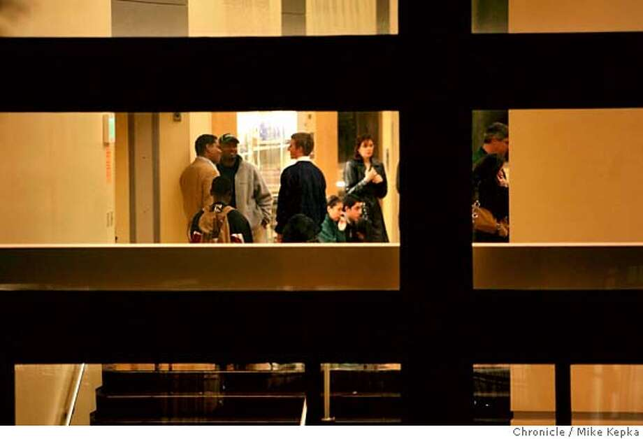 Attendees of the girls basketball game at Sacred Heart Cathedral Prep. wait inside as the San Francisco Police Depart investigates the scene of the crime after a man was shot to death Saturday night in a parking lot across the street from the school. The shooting happened during a girls basketball game against Arch Bishop Mitty from San Jose. Mike Kepka/The Chronicleu Photo: Mike Kepka