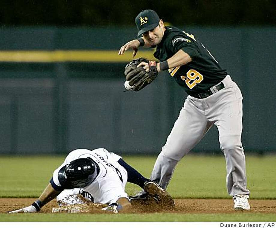 Oakland Athletics second baseman Adam Kennedy (29) drops the ball after getting a force-out on Detroit Tigers' Gerald Laird, left, and trying to turn a double play in the third inning of a game Friday, May 15, 2009, in Detroit. Detroit's Adam Everett was safe at first. Photo: Duane Burleson, AP