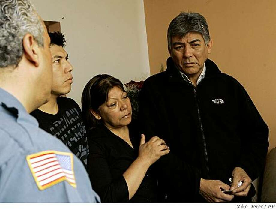 Carlos Bueno, right, and his wife, Eugenia Galdos, center, and their son, Carlos Jr., receive condolences at their home in Paterson, N.J., Wednesday, May 13, 2009, from a Paterson police officer on the death of their son, Sgt. Christian Bueno-Galdos.  Bueno-Galdos, 25, is one of the soldiers who the Army says were gunned down by a comrade in a clinic in Iraq.  (AP Photo/Mike Derer) Photo: Mike Derer, AP