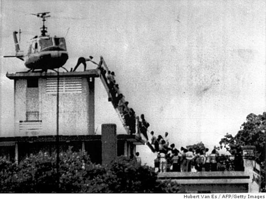 This picture taken in 1975 during the fall of Saigon by the late Dutch photographer Hugh Van Es shows evacuees mounting a staircase to board an American helicopter near the American Embasy in Saigon. Van Es, whose photo of the 1975 fall of Saigon became one of the most enduring images of the Vietnam war, died on May 15, 2009. He was 67.  Van Es suffered a brain haemorrhage last week in Hong Kong, where he had lived for many years, and never regained consciousness, colleagues said. AFP PHOTO / ANP / SPAARNESTAD / HUBERT VAN ES  NO SALES - NO ARCHIVES - RESTRICTED TO EDITORIAL USE       netherlands out - belgium out (Photo credit should read Hubert van Es/AFP/Getty Images) Photo: Hubert Van Es, AFP/Getty Images
