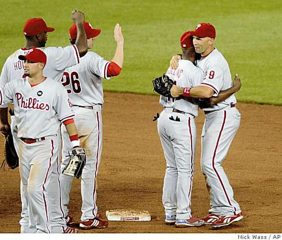 Philadelphia Phillies Raul Ibanez, right, celebrates with Jimmy Rollins, second from right, after the Phillies beat the Washington Nationals 10-6 in 12 innings in a baseball game, Friday, May 15, 2009, in Washington. Also seen are Phillies' Ryan Howard, left, and Chase Utley (26). (AP Photo/Nick Wass) Photo: Nick Wass, AP