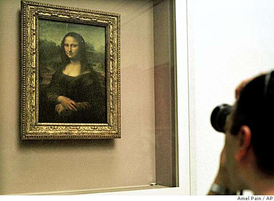 """A man takes a photograph of Leonardo da Vinci's 16th century masterpiece the """"Mona Lisa"""" painting, kept behind a protective glass, in the Louvre museum in Paris in a Monday April 26, 2004 file photo. Photo: Amel Pain, AP"""