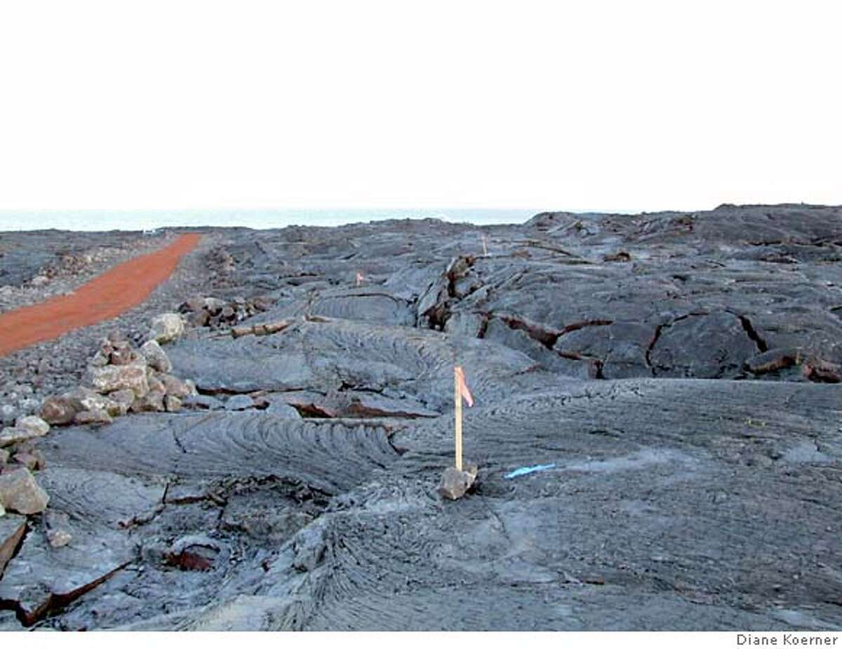 Diane Koerner Filename: lava13_PH1.JPG Content Date: Live Caption: A newly bulldozed road heads toward the Pacific across a lava field near Kalapana. Wooden stakes mark the corners of a lot. The parcel was recently sold by Roger Harris, a real estate agent with Pahoa Realty, a town some 10 miles away. Lots of 7,500 to 10,000 square feet in this area sell for between $15,000 and $20,000, Harris said. This Lava field is less than 20 years old.