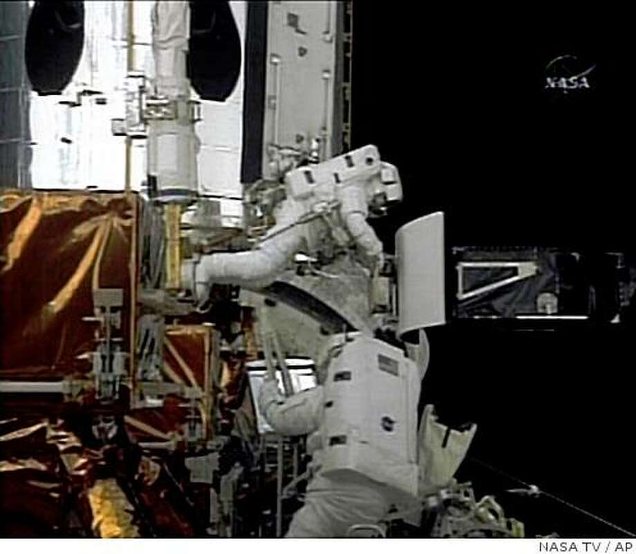 In this image from NASA TV astronauts Drew Feustel, top, and John Grunsfeld  work to upgrade the Hubble Space Telescope during a spacewalk, Thursday, May 14, 2009. (AP Photo/NASA TV) Photo: NASA TV, AP
