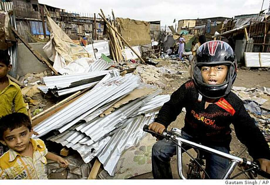 """Slumdog Millionaire"" child star Azharuddin Mohammed Ismail, right, drives a bicycle past demolished shanties in his neighborhood in Mumbai, India, Thursday, May 14, 2009. City workers bulldozed the home of Azharuddin Thursday as part of the demolition of dozens of shanties in a Mumbai slum.(AP Photo/Gautam Singh) Photo: Gautam Singh, AP"