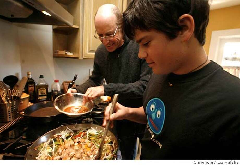 Chez Pollan: UC Berkeley journalism professor and author Michael Pollan (left) adds a little sauce while his son, Isaac Pollan, 15, cooks the stir-fry for lunch at their Berkeley home. Chronicle photo by Liz Hafalia