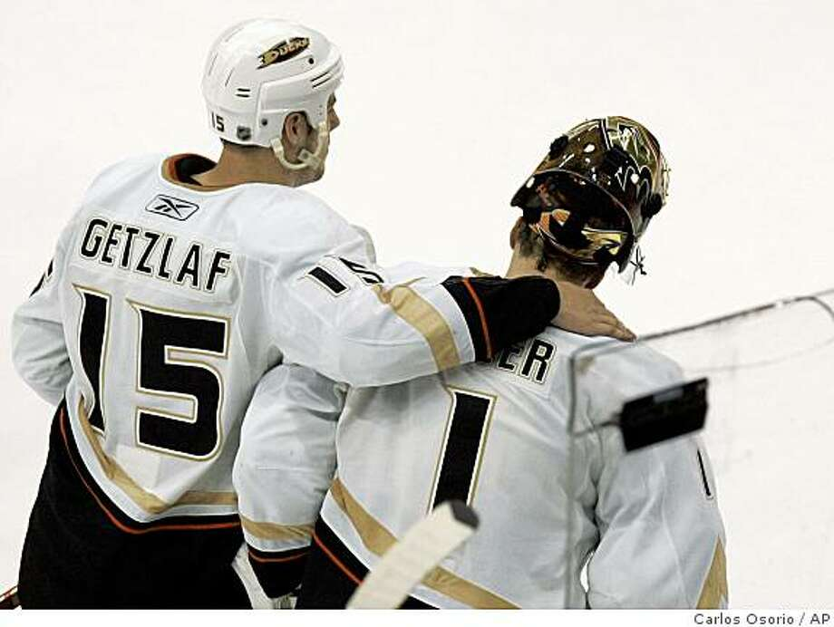 Anaheim Ducks center Ryan Getzlaf (15) skates with goalie Jonas Hiller (1), of Switzerland, after the Ducks' 4-3 loss to the Detroit Red Wings in Game 7 of an NHL hockey Western Conference semifinal series, Thursday, May 14, 2009, in Detroit. (AP Photo/Carlos Osorio) Photo: Carlos Osorio, AP