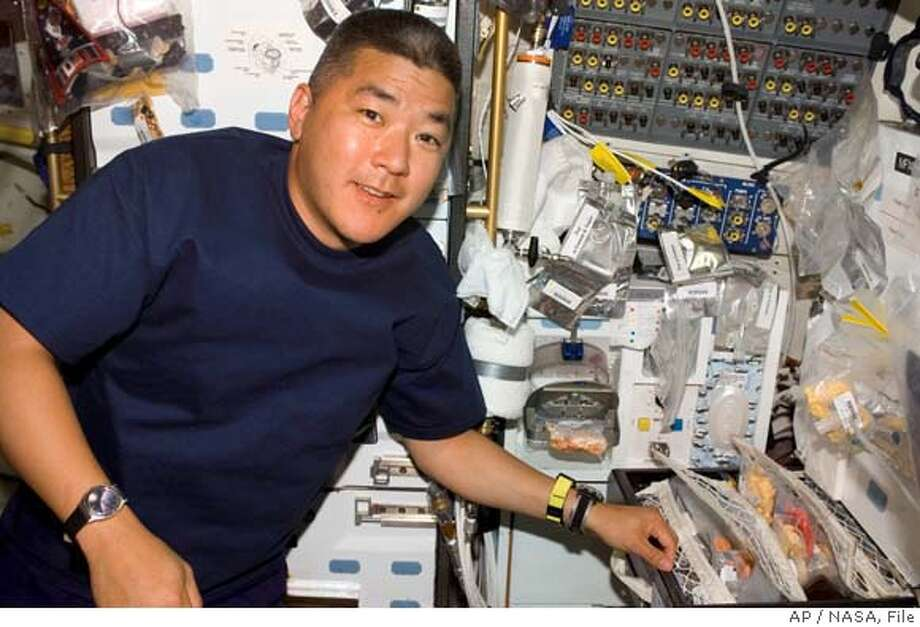 ** FILE ** This photo released by NASA shows astronaut Daniel M. Tani as he prepares to use the galley on the middeck of Space Shuttle Discovery on Oct. 24, 2007. Rose Tani, the 90-year-old mother of Daniel Tani who is aboard the international space station died in Lombard, Ill. on Wednesday Dec. 19, 2007 when a train struck her vehicle, police said. (AP Photo/NASA, File) OCT. 24, 2007 PHOTO Photo: Nasa