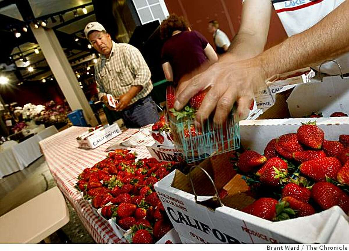 Farmers including Poli Yerena (left) unpack fresh strawberries for the farmers market which opens Friday. The Island Earth Farmer's Market is opening up on the ground floor of the Metreon at 4th and Mission Streets in downtown San Francisco.