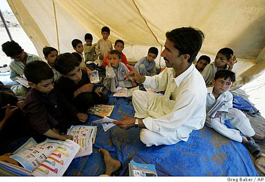 A teacher takes a class in a tent at a refugee camp in Swabi, in northwest Pakistan, Thursday, May 14, 2009. An army offensive against Taliban insurgents in the Swat Valley area has driven at least 800,000 people from their homes, with 80,000 staying in several camps south of the battle zone. Prime Minister Yousuf Raza Gilani told parliament Thursday that it was the largest internal displacement of Pakistanis since the country's creation in 1947.   (AP Photo/Greg Baker) Photo: Greg Baker, AP