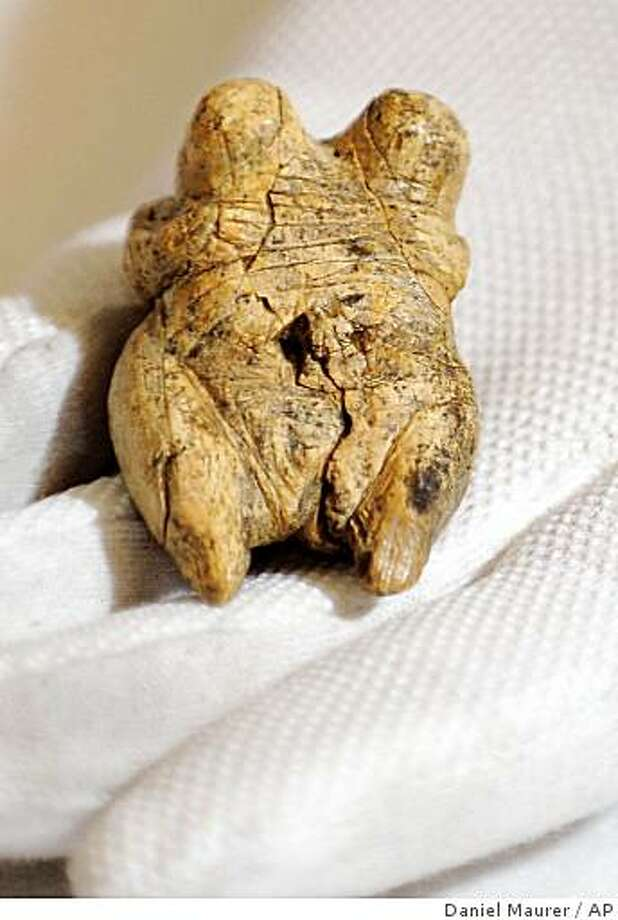 A carved ivory female figurine is presented in Tuebingen, southern Germany, Wednesday, May 13, 2009. The figurine, found in 2008 in a cave in Schelklingen, southern Germany is allegedly the world's oldest  reproduction of a human with an estimated age of at least 35,000 years. (AP Photo/Daniel Maurer) Photo: Daniel Maurer, AP