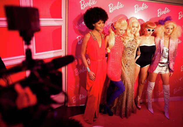 Models dressed as Barbie dolls pose for the media at the Barbie Dream House ...