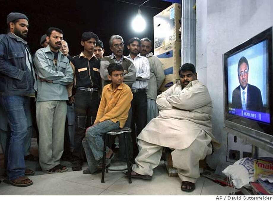 Pakistanis watch President Pervez Musharraf speak to the nation on televison in Karachi Wednesday, Jan. 2, 2008. Musharraf said Wednesday that he had requested a team of investigators from Britain's Scotland Yard to assist in the investigation into the killing of opposition leader Benazir Bhutto.(AP Photo/David Guttenfelder) Photo: David Guttenfelder