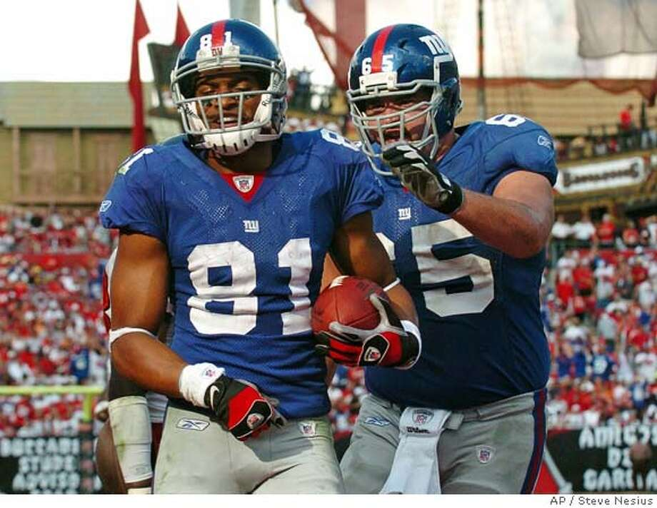 New York Giants' Gary Ruegamer (65) congratulates teammate Amani Toomer (81) after Toomer's touchdown-reception from quarterback Eli Manning during the third quarter of their NFL wild-card playoff football game against the Tampa Bay Buccaneers Sunday, Jan. 6, 2008, in Tampa, Fla. New York won, 24-14. (AP Photo/Steve Nesius) EFE OUT Photo: Steve Nesius