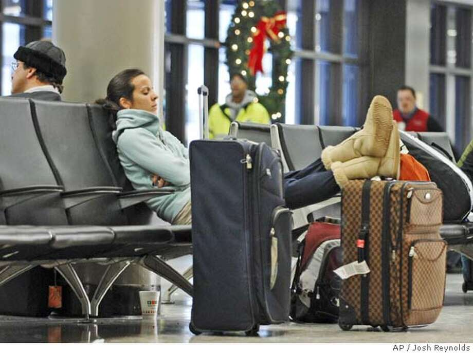 Angela Amaro rests and waits for her ride after arriving on a flight from Honolulu at Logan International Airport Friday, Dec. 21, 2007, in Boston. She made the holiday trip to visit relatives in Taunton, Mass. (AP Photo/Josh Reynolds) Photo: Josh Reynolds