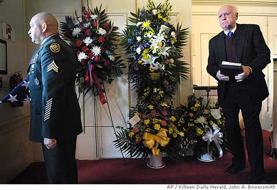Sgt. Lonnie Tettaton, left, holds Cpt. Rowdy J. Inman's ceremonial flag until it is presented to his family while Dr. Sam Canine leaves the chapel at the end of a memorial service at Harper-Talasek Funeral Home in Killeen, Texas Friday Jan. 4, 2008. Inman died Dec. 26, 2007, in Iraq while serving with the Third Armored Calvary Division. (AP Photo/ Killeen Daily Herald, John A. Bowersmith) Photo: John A. Bowersmith