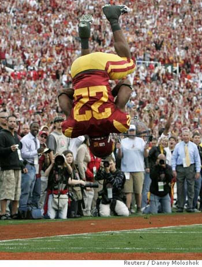 University of Southern California's Trojans Desmond Reed (22) does a flip as he crosses the goal line to score a first quarter touchdown against the Illinois Fighting Illini's during the 94th Rose Bowl Game in Pasadena, California January 1, 2008. REUTERS/Danny Moloshok (UNITED STATES) Photo: DANNY MOLOSHOK