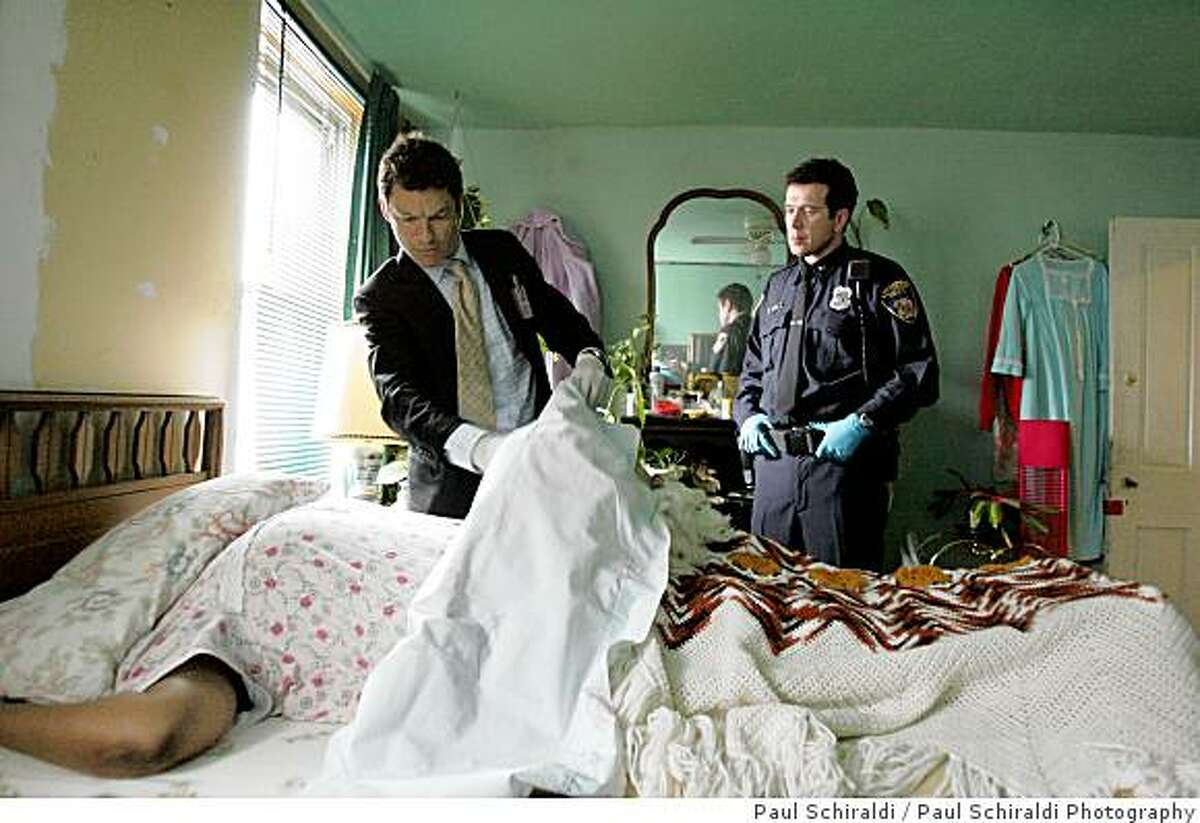 McNulty takes in the crime scene with Officer Bobby Brown. THE WIRE: Dominic West, Bobby Brown.