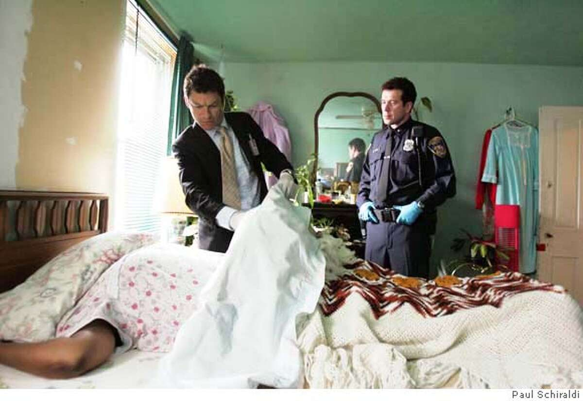 McNulty takes in the crime scene with Officer Bobby Brown. THE WIRE: Dominic West, Bobby Brown. Paul Schiraldi