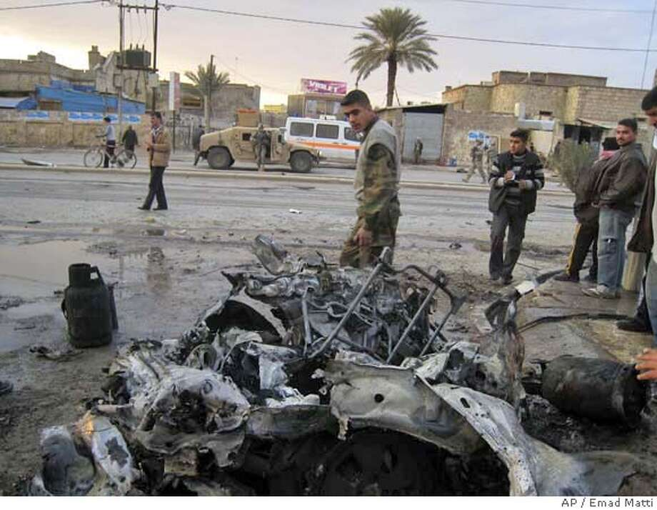 Men inspect the damage after two car bombs exploded in Kirkuk, 290 kilometers (180 miles) north of Baghdad, Iraq on Wednesday, Jan. 9, 2008. A parked car bomb exploded Wednesday afternoon near the Heart Of Jesus church in central Kirkuk, wounding one civilian; ten minutes later, another parked car bomb detonated next a church nearby, wounding two civilians, police said.(AP Photo/Emad Matti) Photo: EMAD MATTI