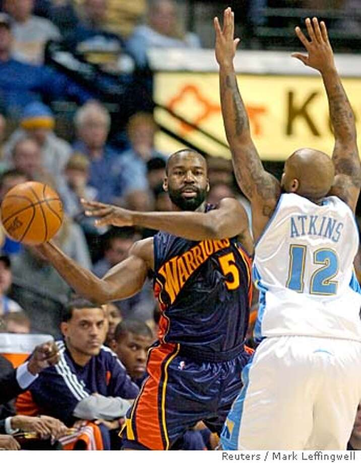 Golden State Warriors Baron Davis (L) passes the ball while being guarded by Denver Nuggets Chucky Atkins (R) during their NBA basketball game in Denver, Colorado December 30, 2007. REUTERS/Mark Leffingwell (UNITED STATES) Photo: MARK LEFFINGWELL