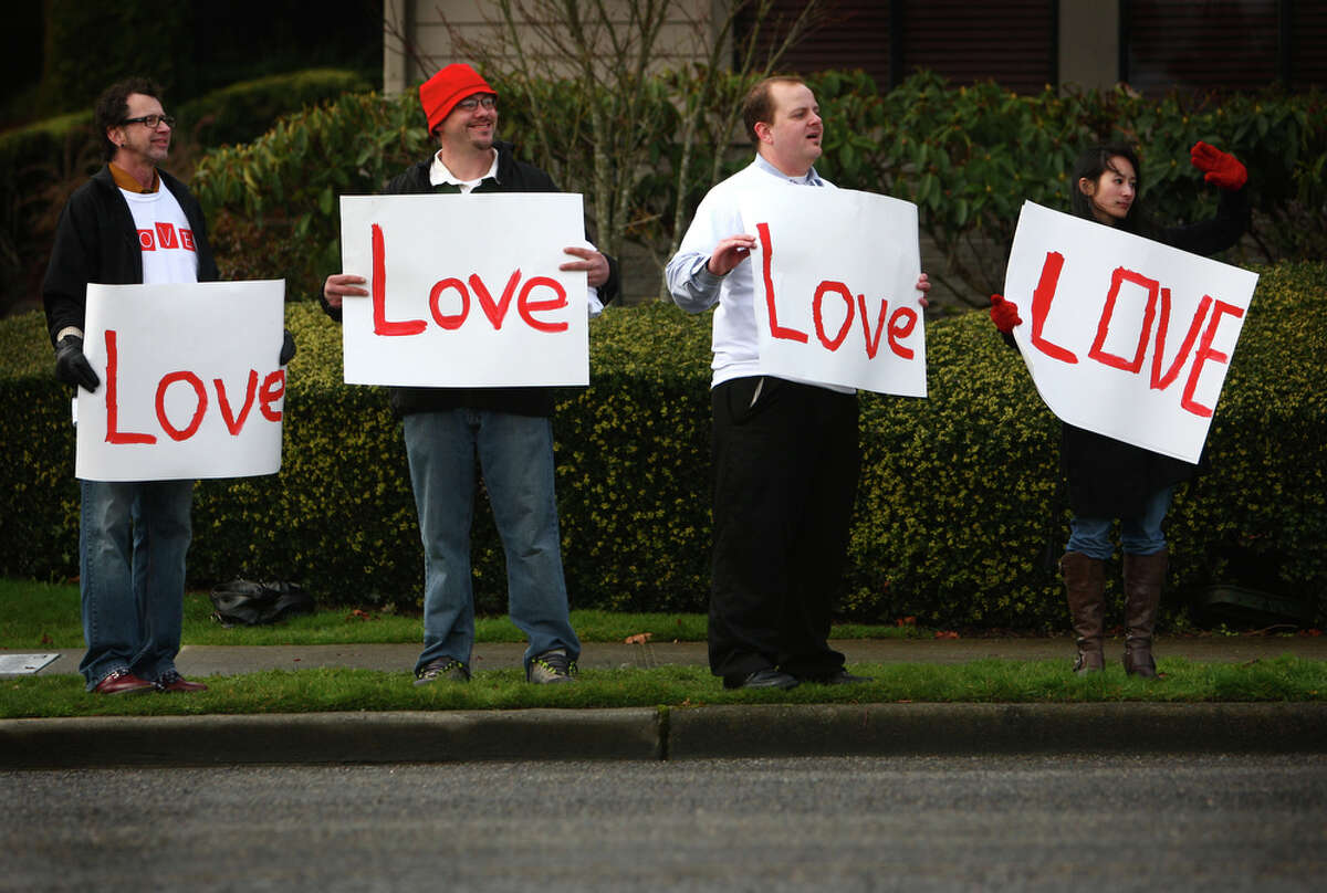From left, Dino Macioci, Joey Adams, Owen Anderson and Stacy Chan, all of Tacoma, hold signs outside the Life Center church on Saturday, February 11, 2012 in Tacoma after the funeral for Braden and Charlie Powell. The boys were killed by their father Josh Powell during a supervised visit near Graham, Wash.