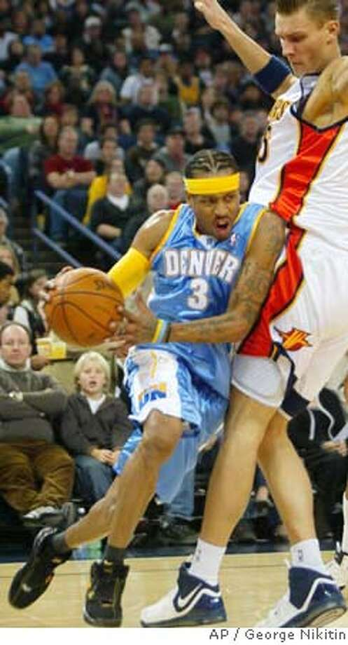 Denver Nuggets' Allen Iverson, left, drives for the bucket past Golden State Warriors' Andris Biedrins,of Latvia, in the first half of an NBA basketball game, Friday, Dec. 28, 2007 in Oakland, Calif. (AP Photo/George Nikitin) Photo: George Nikitin