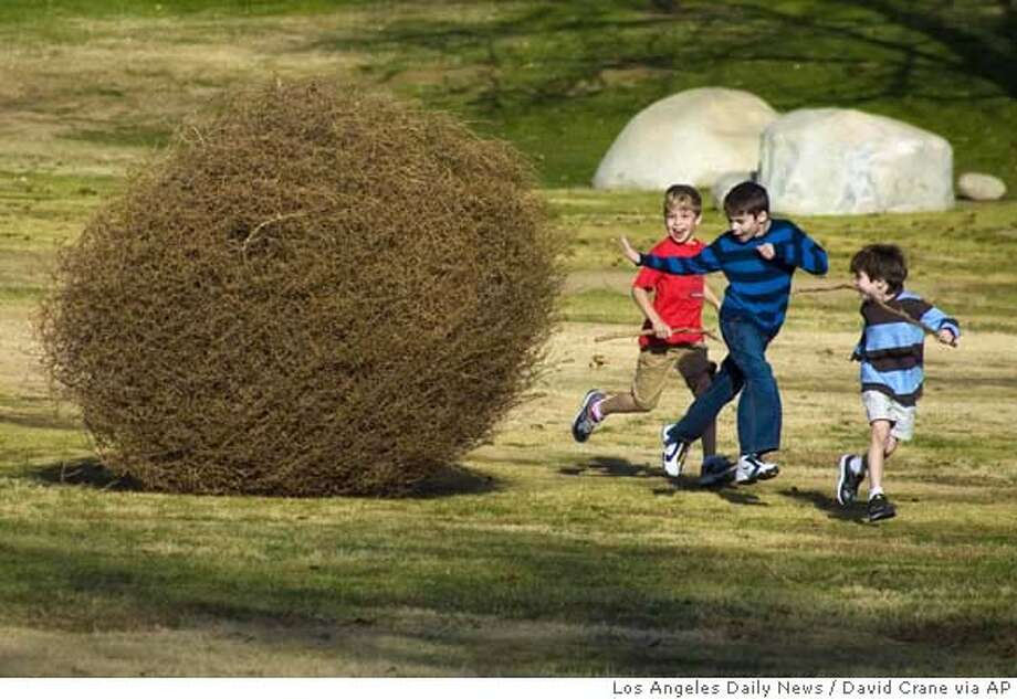 ** CORRECTS CITY TO LOS ANGELES ** A group of children run from a large tumbleweed pushed by strong winds in the Sepulveda Dam Recreation area in Van Nuys in the San Fernando Valley in Los Angeles on Sunday, Dec. 23, 2007. (AP Photo/Los Angeles Daily News, David Crane) ** MANDATORY CREDIT; LA TIMES OUT, VENTURA COUNTY STAR OUT, NEWHALL SIGNAL OUT, ANTELOPE VALLEY PRESS OUT, NO MAGS, NO SALES ** MANDATORY CREDIT; LA TIMES OUT, VENTURA COUNTY STAR OUT, NEWHALL SIGNAL OUT, ANTELOPE VALLEY PRESS OUT, NO MAGS, NO SALES Photo: David Crane
