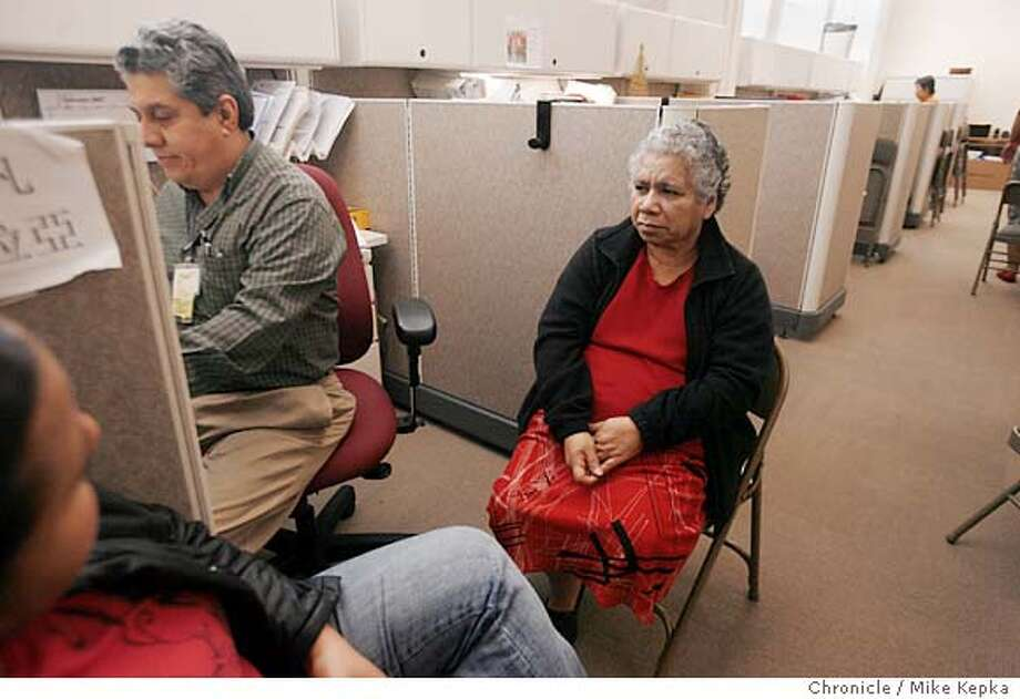 Ivan Zelaya, in the San Francisco eligibility unit, completes the final paperwork to sign Juana Conejo, 63, up for Health San Francisco. Conejo has no other insurance, and two years too young to qualify for Medicaid. - San Francisco's ground-breaking plan to provide healthcare for all its uninsured residents expanded significantly on Wednesday, as it allowed city residents earning up to $30,000 a year to enroll. Photo taken on 1/2/08, in San Francisco, CA, USA  Ran on: 01-03-2008  Ivan Zelaya at the new eligibility office completes the paperwork that Juana Conejo will sign to join Healthy San Francisco. Photo: Mike Kepka