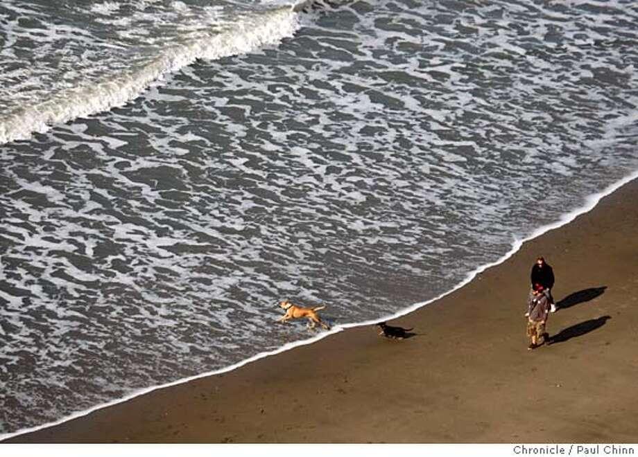 People and their pets walk along the surf while enjoying the calm before the storm at Fort Funston in San Francisco, Calif. on Wednesday, Jan. 2, 2008. Weather forecasters are predicting a series of heavy rain storms that are expected to drench the region through the weekend.  PAUL CHINN/The Chronicle MANDATORY CREDIT FOR PHOTOGRAPHER AND S.F. CHRONICLE/NO SALES - MAGS OUT Photo: PAUL CHINN