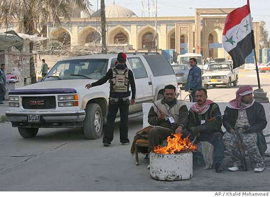 Security volunteers warm themselves by a fire as another volunteer checks a vehicle entering the primarily Sunni Azamiyah neighborhood of north Baghdad, Iraq on Sunday, Dec. 23, 2007. Iraq's Shiite-led government has said that American-backed Sunni groups key to battling Islamic extremists will not be allowed to become a separate military force and must be eventually disbanded.(AP Photo/ Khalid Mohammed) Photo: KHALID MOHAMMED