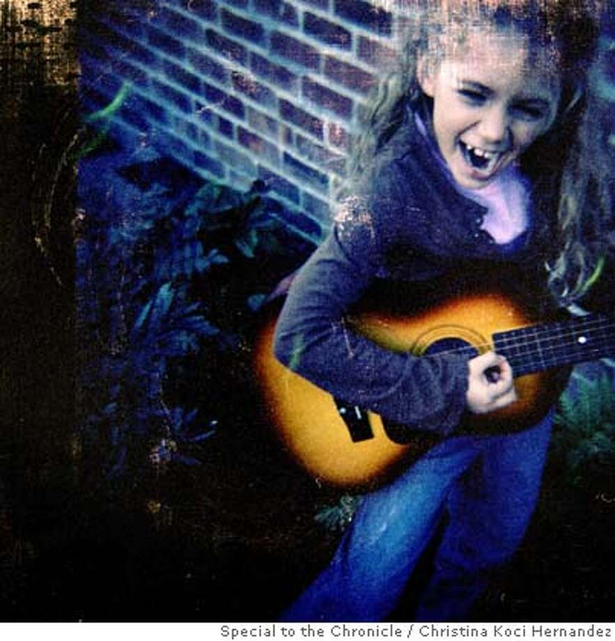 Fiona, age 6, plays her guitar, in the family yard. Christine Carter McLaughlin, photographed with her two daughters, Fiona,6, and Amalia,4, in her Piedmont home. She is a teacher of optimism and head of the Center for Greater Good at Berkeley  Ran on: 12-30-2007  Fiona McLauglin, 6, strums the guitar in her Piedmont backyard.  Ran on: 12-30-2007 Photo: Christina Koci Hernandez