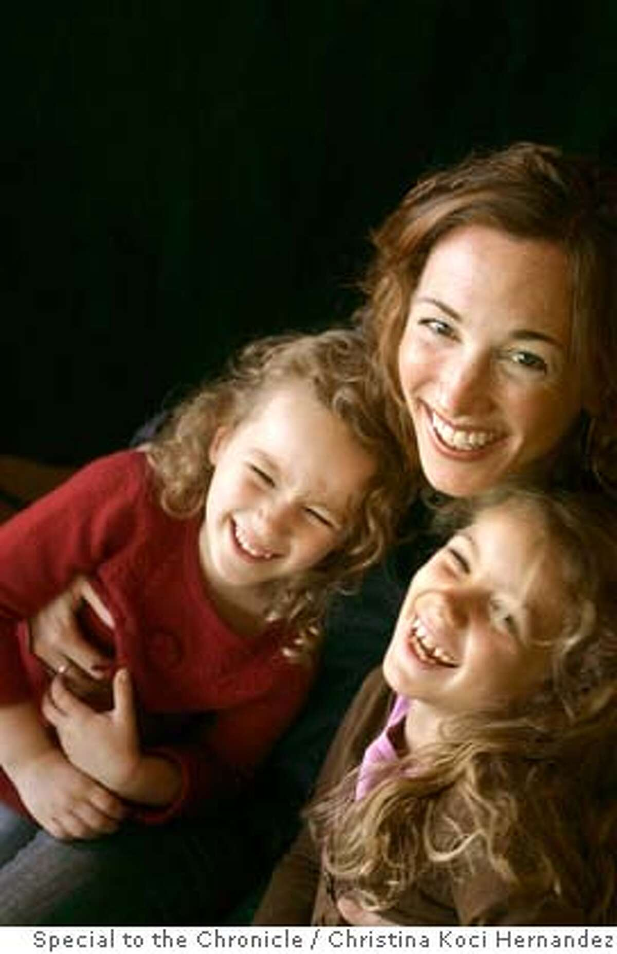 Christine Carter McLaughlin, photographed with her two daughters,(R) Fiona,6, and (L)Amalia,4, in her Piedmont home. She is a teacher of optimism and head of the Center for Greater Good at Berkeley Ran on: 12-30-2007 Fiona McLauglin, 6, strums the guitar in her Piedmont backyard.