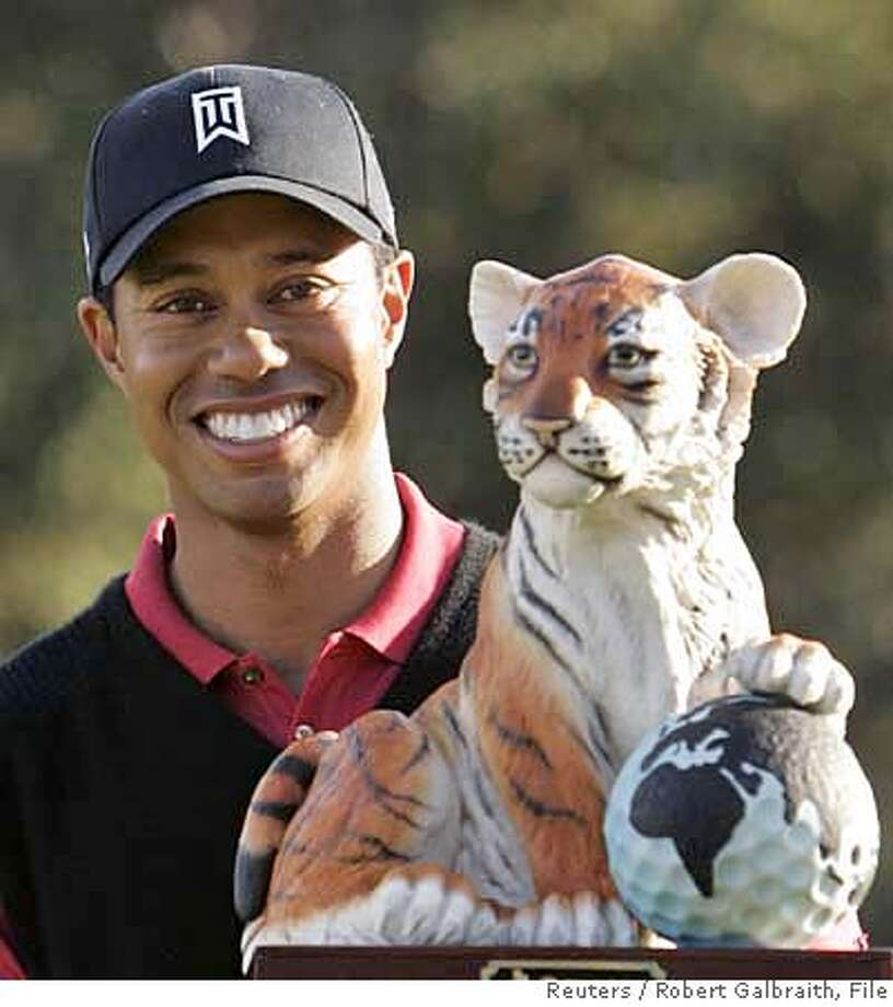 U.S. golfer Tiger Woods poses with the winner's trophy after capturing the Target World Challenge golf tournament in Thousand Oaks, California December 16, 2007. REUTERS/Robert Galbraith (UNITED STATES) 0 Photo: ROBERT GALBRAITH
