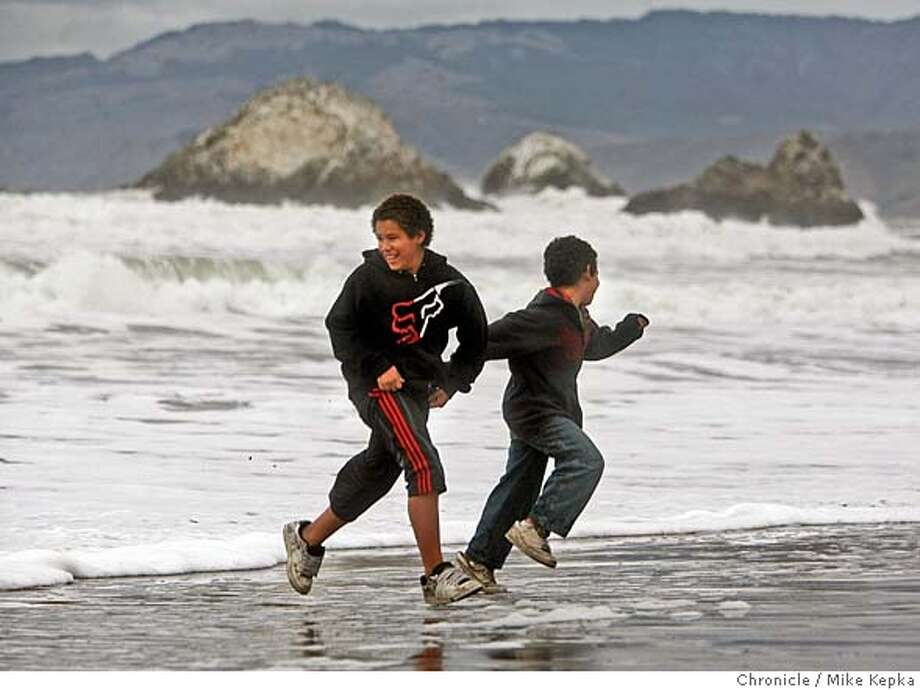 Enjoying the holiday break from school, Andrew James, 11, and his brother Michael James, 9, of Cupertino, Calif. dodge waves at Ocean Beach in San Francisco. Mike Kepka / The Chronicle Photo taken on 12/27/07, in San Francisco, CA, USA MANDATORY CREDIT FOR PHOTOG AND SAN FRANCISCO CHRONICLE/NO SALES-MAGS OUT Photo: Mike Kepka