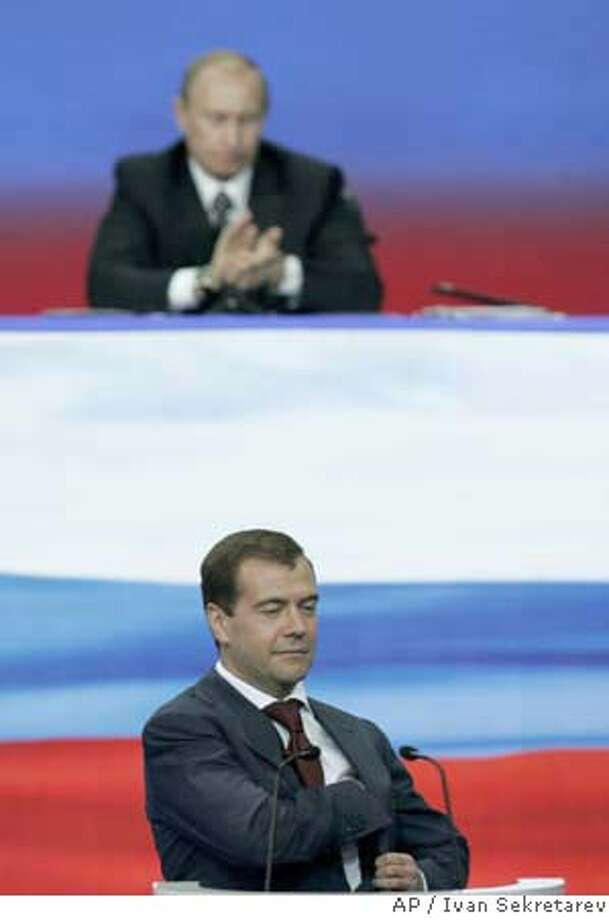 With President Vladimir Putin in the background his longtime protege Dmitry Medvedev smiles during a United Russia party congress in Moscow, Monday, Dec. 17, 2007. Putin told the party congress Monday that he would accept the prime minister's post if Medvedev is elected president, guaranteeing Putin a heavyweight political role after he leaves the presidency in May. (AP Photo/Ivan Sekretarev) Photo: IVAN SEKRETAREV