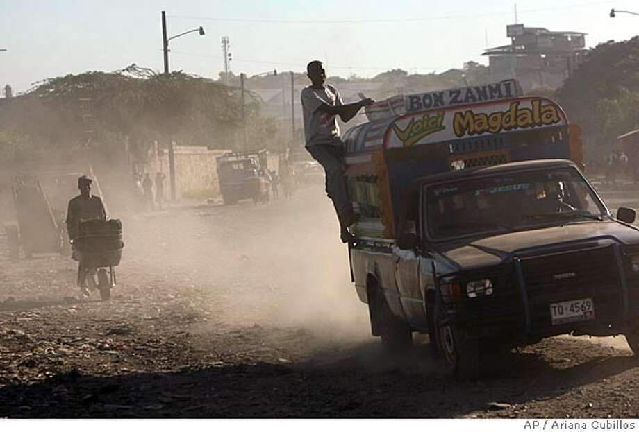 A man rides on the back of a public transportation van called 'TAP TAP' in Port-au-Prince, Friday, Nov. 30, 2007. Haiti is by far the poorest country in the Western hemisphere, with poverty levels approaching those of parts of Africa and southeast Asia. About 80% of the population lives in abject poverty, engaged mainly in subsistence agriculture. (AP Photo/Ariana Cubillos) Photo: Ariana Cubillos